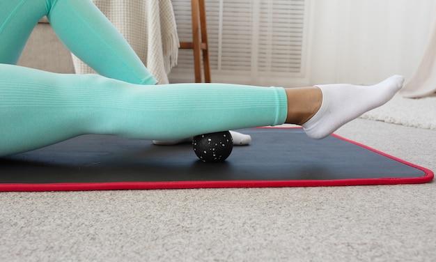Montare sportivo da donna nera che indossa abbigliamento sportivo roll on foam massaggio miofasciale rullo massaggiante muscolare