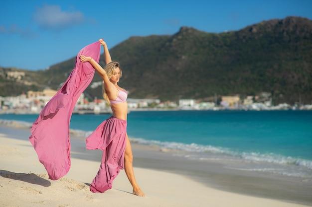 Ragazza in forma e sportiva in posa su una spiaggia. viaggi, libertà, felicità, vacanza, vacanza, concetto