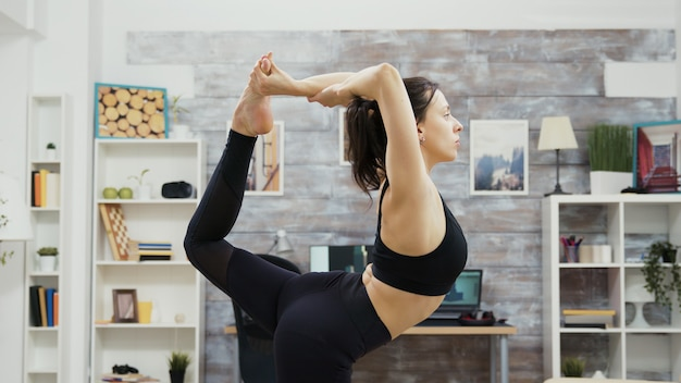 Donna adatta e super flessibile che sta nella posa di yoga. postura yoga.