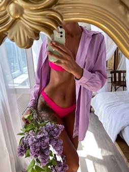 Una donna abbronzata in forma con un corpo perfetto scatta una foto selfie sul telefono nello specchio di casa