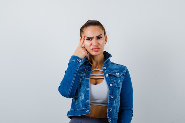 Fit donna in crop top, giacca di jeans, leggings in piedi in posa pensante, mettendo il dito indice sulla tempia e guardando pensieroso, vista frontale.