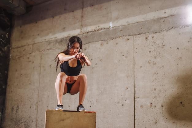 Donna adatta che fa un esercizio di salto della scatola. donna muscolare che fa un edificio occupato in palestra