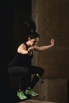 Donna adatta che fa scatola che salta alla palestra del crossfit