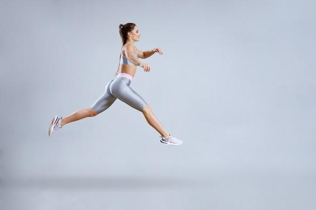 Donna adatta che fa allenamento cardio in palestra. la donna in abiti sportivi sta saltando. concetto di fitness club. isolato su grigio