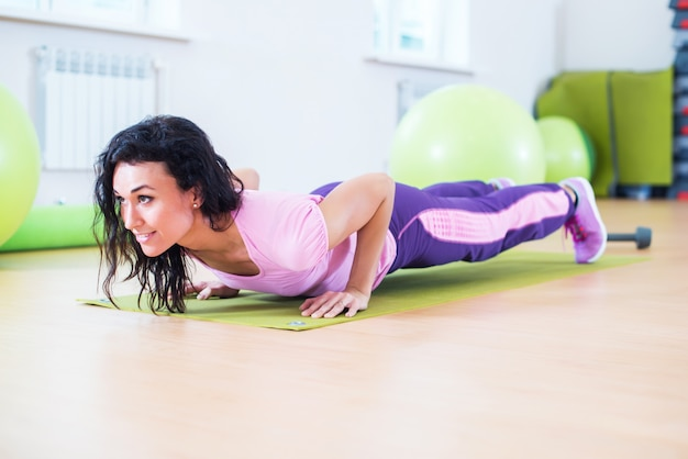 Donna adatta che fa esercizio della plancia e push up lavorando sul tricipite dei muscoli addominali.
