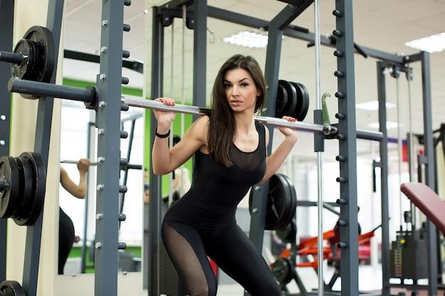 Montare la donna facendo squat con un bilanciere nella macchina smith