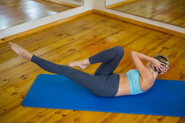 Montare la donna facendo esercizio di stretching sulla stuoia