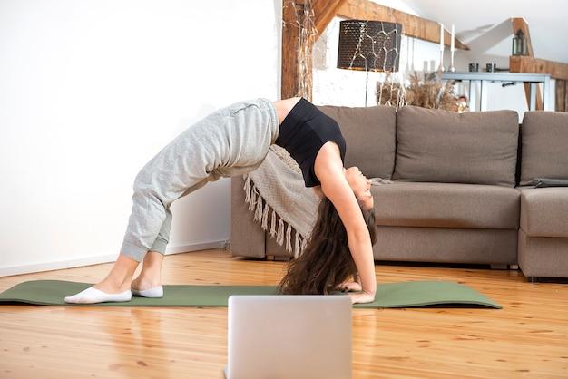 Montare la donna che fa la posa del ponte di esercizio di yoga e guarda i tutorial online sul laptop, la formazione in casa