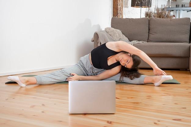 Montare la donna facendo esercizi di yoga e guardando tutorial online sul laptop, formazione nel soggiorno di casa