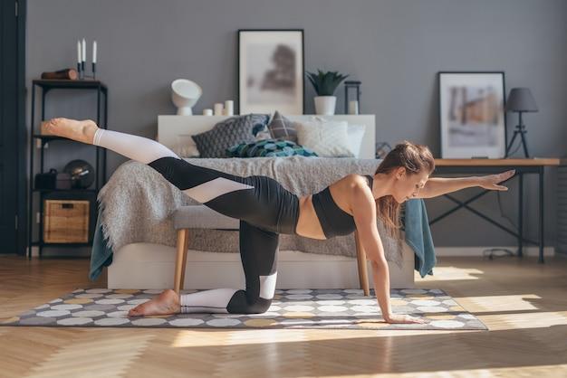 Montare la donna che esercita a casa a praticare yoga.