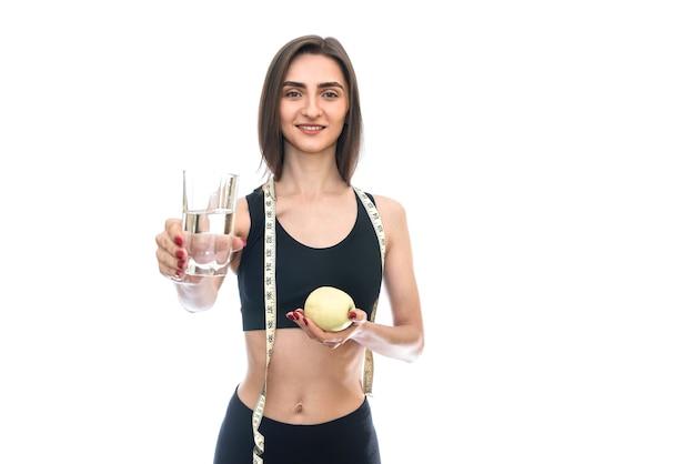 Donna adatta che tiene mela e bicchiere d'acqua isolati su bianco