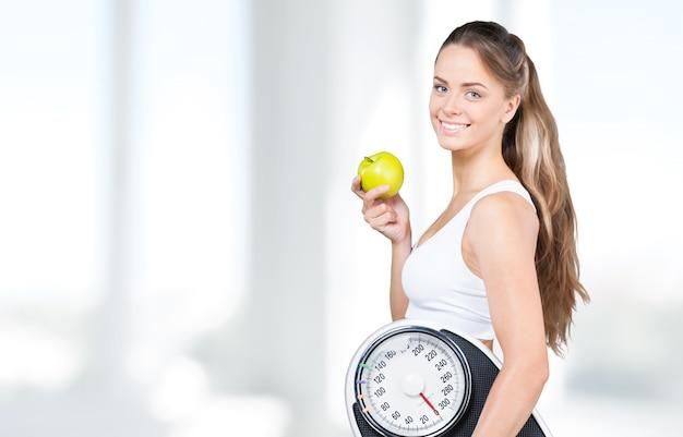 Donna in forma che tiene una bilancia e una mela