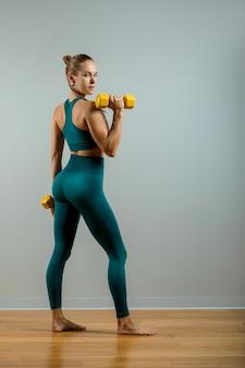 Donna adatta sollevamento pesi bella ragazza fitness in posa con manubri