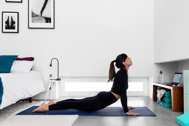 Fit donna pratica cobra posa utilizzando il programma di formazione yoga online nel laptop a casa