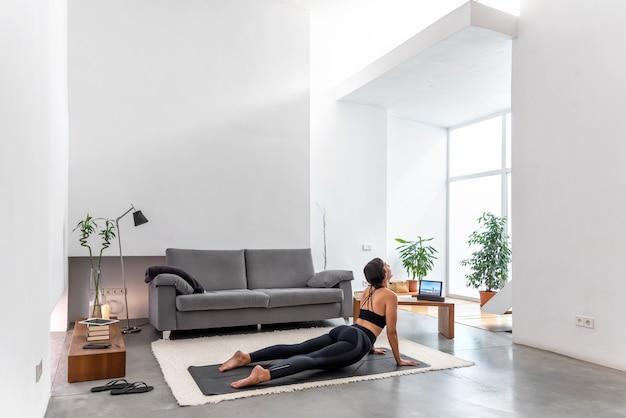 Posa adatta della pratica della cobra della donna facendo uso del programma online di addestramento di yoga nella compressa a casa