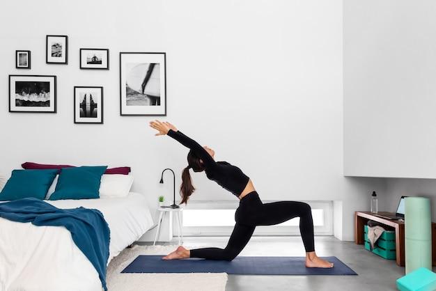 Montare la donna che pratica la posa della mezza luna utilizzando il programma di formazione yoga online nel laptop a casa
