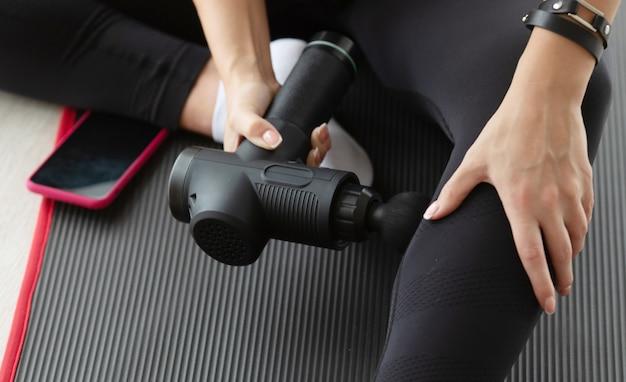 Donna adatta che pratica la tecnica di automassaggio per i glutei applicando una pistola per massaggio percussivo terapeutico therapeutic