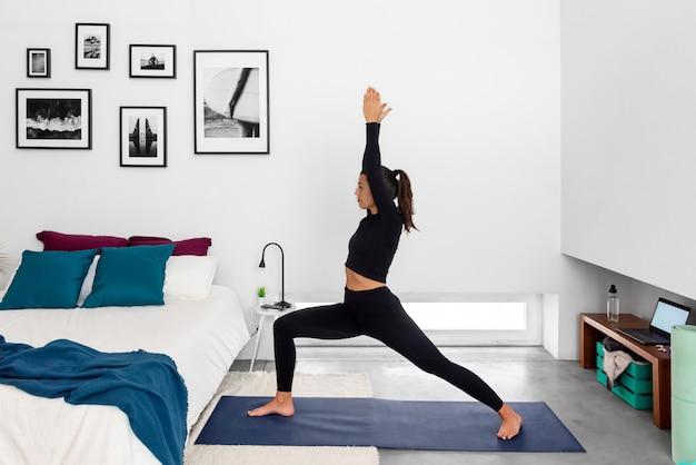 Donna adatta che pratica il guerriero che posa usando il programma di addestramento di yoga in linea nel laptop a casa