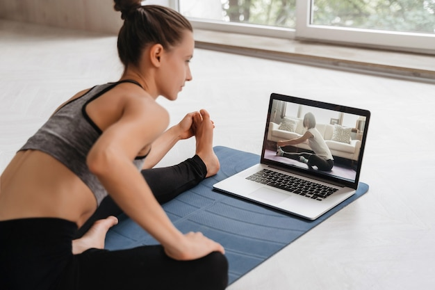 Montare la donna in abiti sportivi che fa yoga sulla stuoia di esercizio a casa utilizzando laptop guardando tutorial. l'allenatore femminile ha una lezione di yoga virtuale sul computer