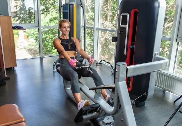 Donna adatta in abbigliamento sportivo che tira la macchina del peso del cavo della corda che risolve per il muscolo del braccio e della schiena. body building e concetto di salute.