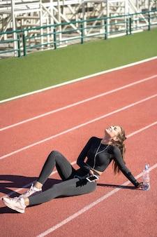 Montare la donna in abiti sportivi che riposa dopo l'allenamento o la corsa