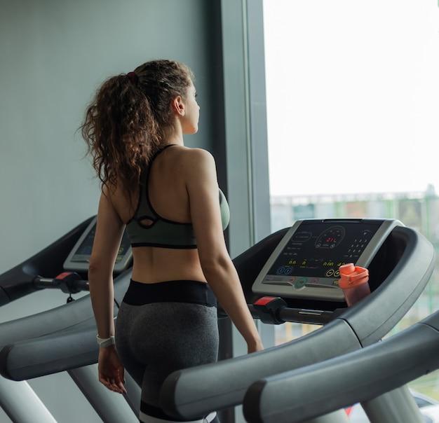 Fit donna in abbigliamento sportivo corre su un tapis roulant e guarda il suo orologio in palestra. il concetto di uno stile di vita sano, riscaldamento, fitness, perdita di peso.