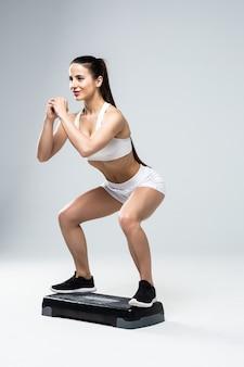 Montare la donna in abiti sportivi al corso di aerobica step isolato su priorità bassa bianca