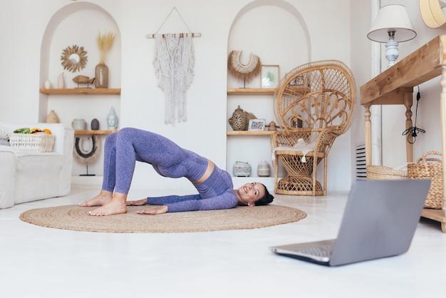 La donna in forma si allena a casa e fa esercizio con il ponte gluteo.
