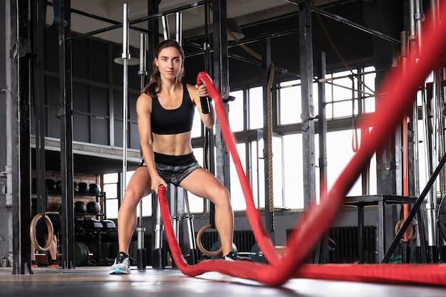 Donna in forma che utilizza corde da battaglia durante l'allenamento della forza in palestra.