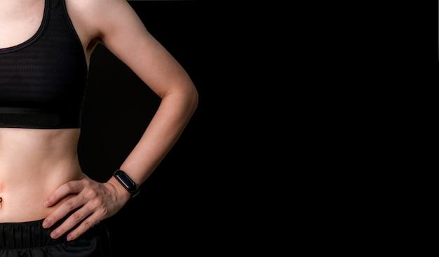 Montare la donna indossare reggiseno sportivo nero e fascia intelligente pronta per l'esercizio. ragazza sportiva attiva. allenamento donna per forza e muscoli forti. braccialetto cardiofrequenzimetro. uno stile di vita sano.