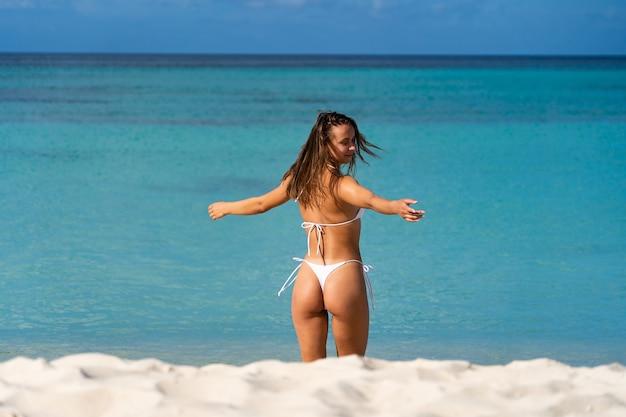 Montare la donna in bianco seduto sulla spiaggia e godersi il sole, la sabbia bianca e l'acqua cristallina del mare azzurro