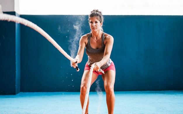Donna adatta con la corda di battaglia nella palestra di forma fisica di addestramento