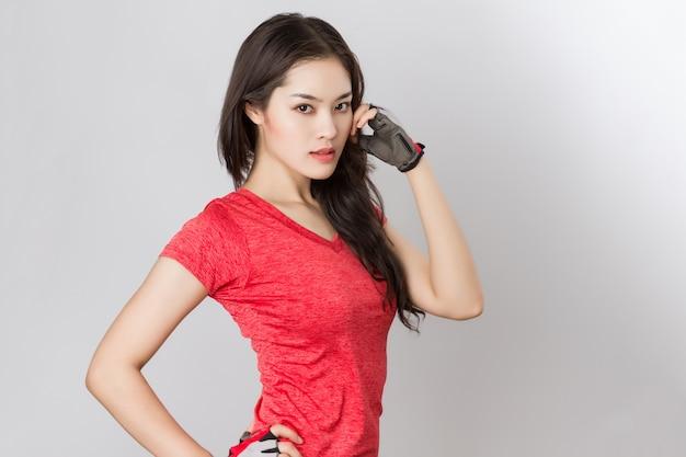 Montare la giovane bella donna asiatica in buona salute con abbigliamento sportivo rosso e guanti.