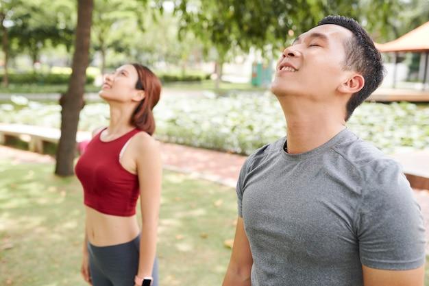 Giovani in forma che respirano aria fresca quando si allenano nel parco cittadino