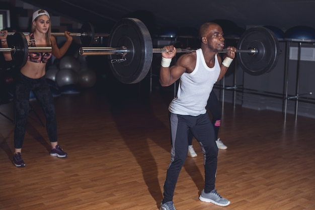 Montare i giovani sollevando i bilancieri sopra la testa, cercando di concentrarsi, allenandosi in palestra con altre persone