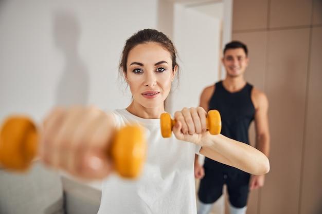 Giovane donna in forma che fa allenamento per le braccia con il suo ragazzo