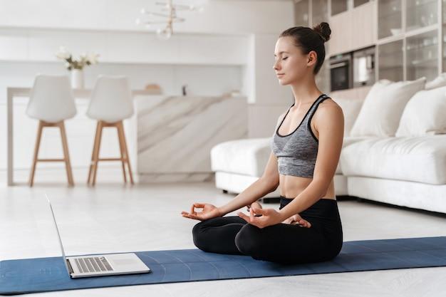Montare la giovane donna che pratica la meditazione a casa sul tappetino per esercizi nel suo salotto