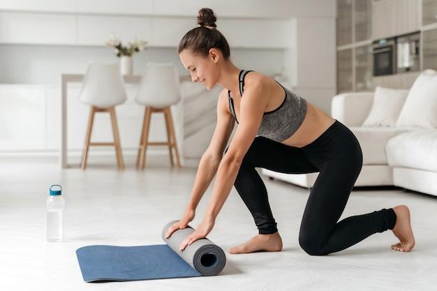 Montare la giovane donna che srotola il materassino yoga e si prepara per un allenamento fitness o una lezione di yoga a casa
