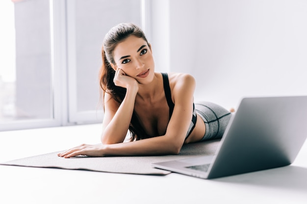 Giovane donna in forma che guarda tutorial online sul laptop, si allena in soggiorno