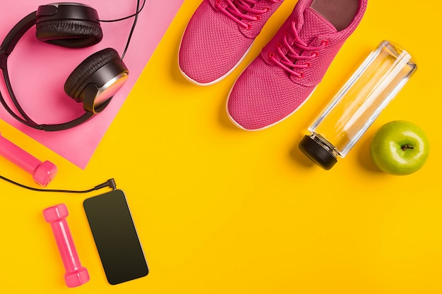 Accessori per il fitness su sfondo giallo. scarpe da ginnastica, bottiglia d'acqua, cuffie e smart. vista dall'alto. natura morta. copia spazio
