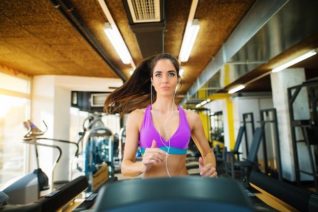 Bella ragazza attiva fitness in esecuzione sul tapis roulant e guardando dritto in palestra.