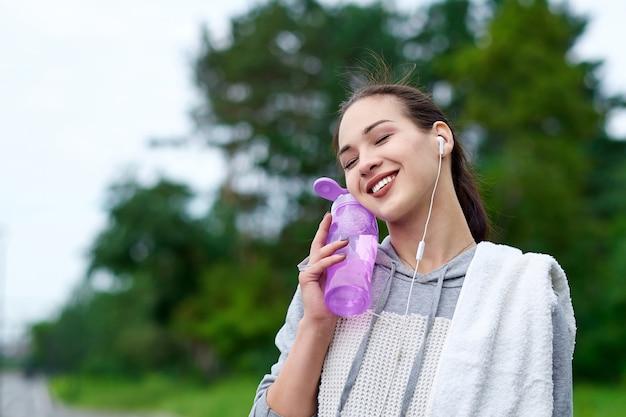 Donna asiatica fitness con bottiglia e asciugamano d'acqua dopo l'allenamento in esecuzione nel parco estivo