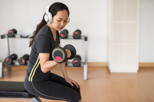 Fitness donna asiatica allenarsi con manubri e ascoltare musica da auricolare in palestra.