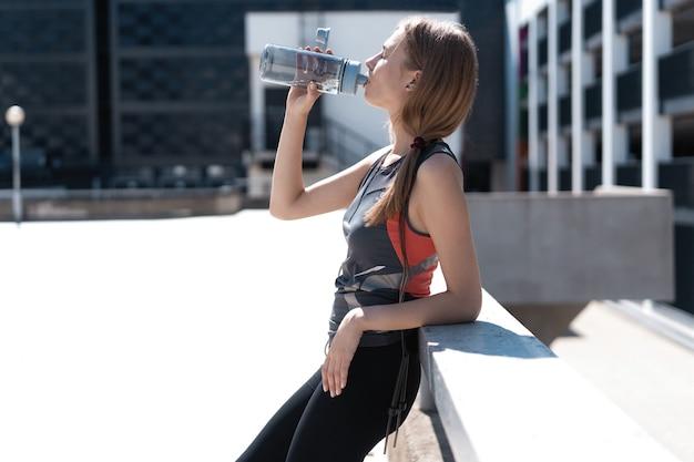 Acqua potabile della donna dell'atleta di forma fisica durante la pausa di allenamento cardio. concetto di idratazione per una vita sana.
