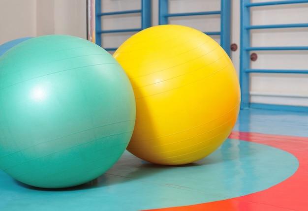 Palle fitness colori verde, giallo e bianco situati sul pavimento in palestra attrezzature sportive per lo yoga
