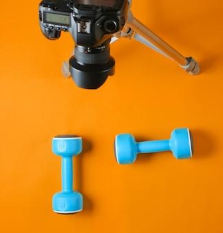 Blogger di fitness. concetto di sport. manubri in plastica e una fotocamera su un treppiede su sfondo arancione. vista dall'alto