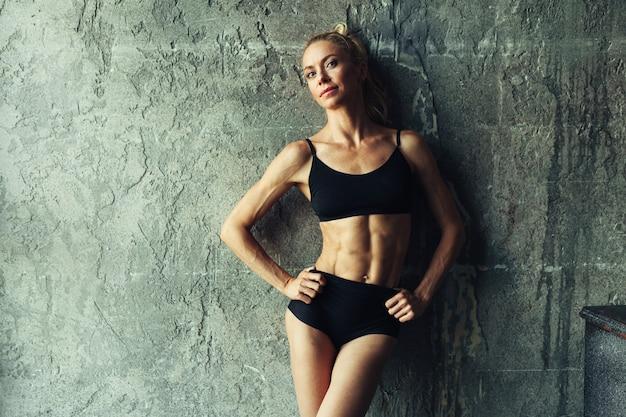 Donna del blondie di forma fisica che sta vicino alla parete