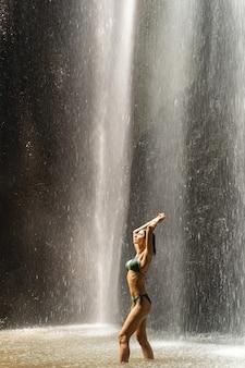 Corpo di forma fisica. gentile ragazza sportiva in piedi in semi posizione e alzando entrambe le mani, godendosi il momento