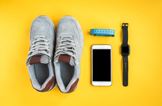 Braccialetto fitness, scarpe da ginnastica, telefono cellulare e nastro su sfondo giallo. allenamento disteso