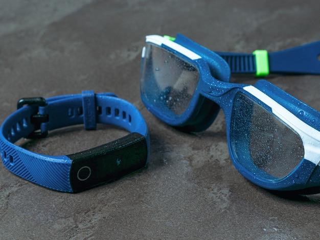 Bracciale fitness con occhiali da nuoto su uno sfondo di pietra. accessori per il nuoto in piscina.